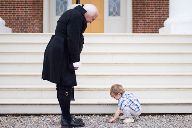 young boy picking up stones in front of James Madison portrayer